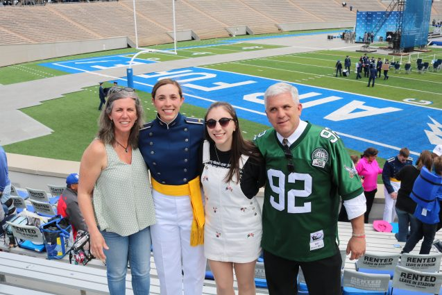 family photo in front of football field