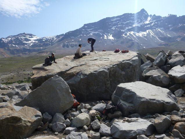 scientists sitting on large boulder