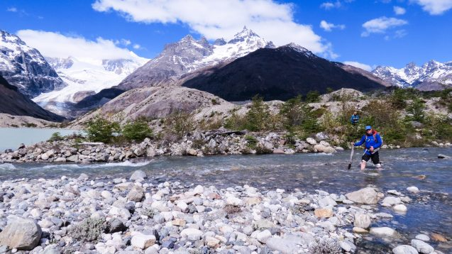 scientist crossing river with mountains in the background