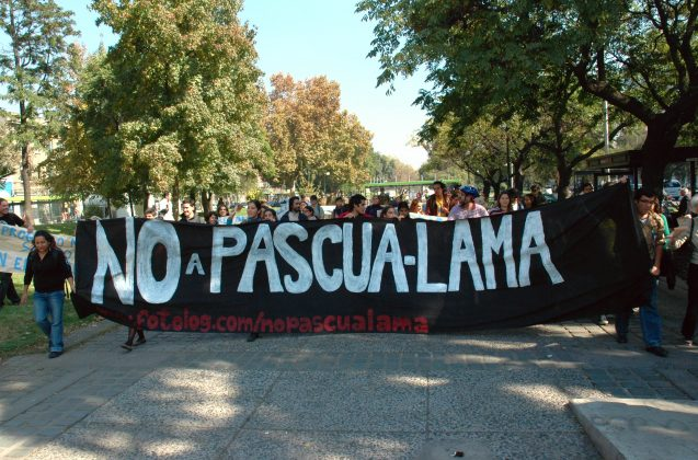 "A crowd of people carry a black banner that reads ""No a Pascua-Lama"" in white letters."