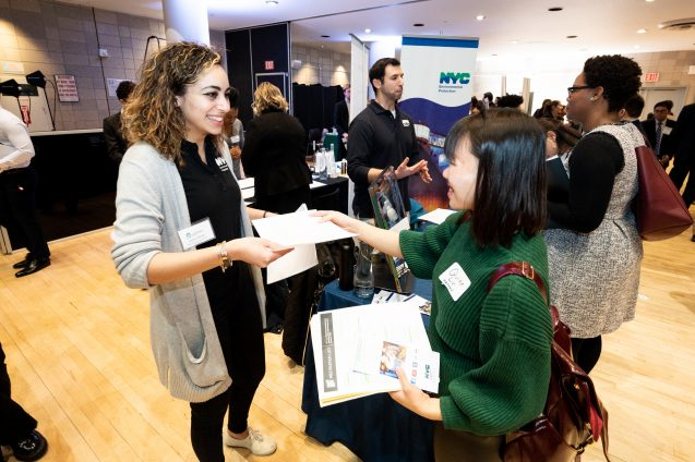 people exchanging papers at all ivy career fair