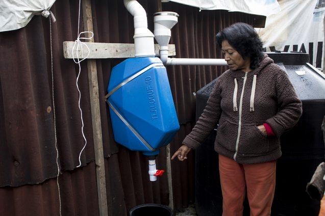 resident stands near rainwater harvesting system