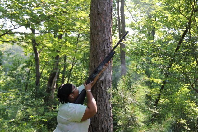 patterson pointing a shotgun up into the tree canopy