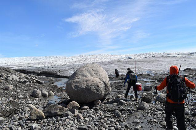 researchers walk across rocky terrain near edge of ice sheet