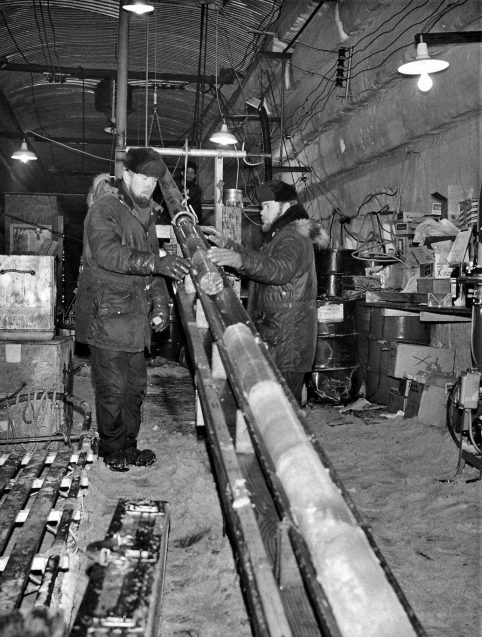 black and white photo of engineers with an ice core
