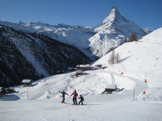 Three people in skis stand in front of a ski run and mountains of the Alps.