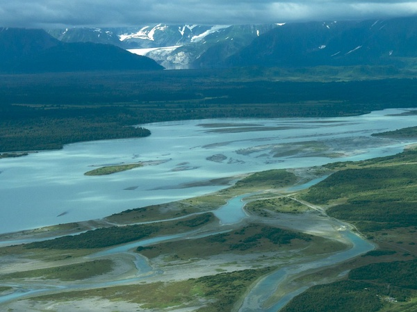 A pale blue river snakes through green earth, making small islands and inlets. Snowcapped mountains rise in the distance.