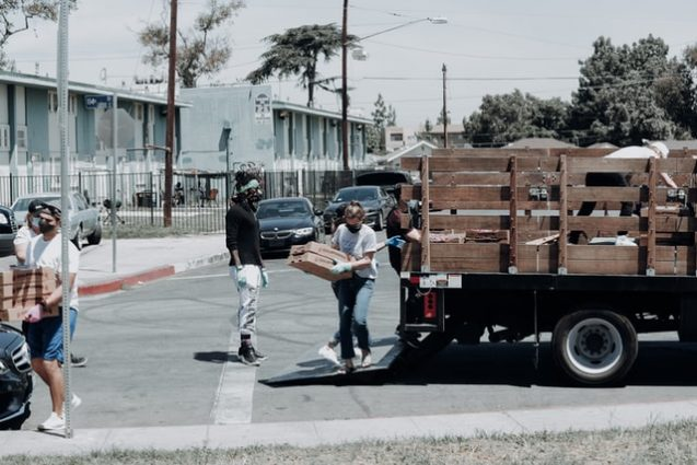 people carrying food boxes from a truck