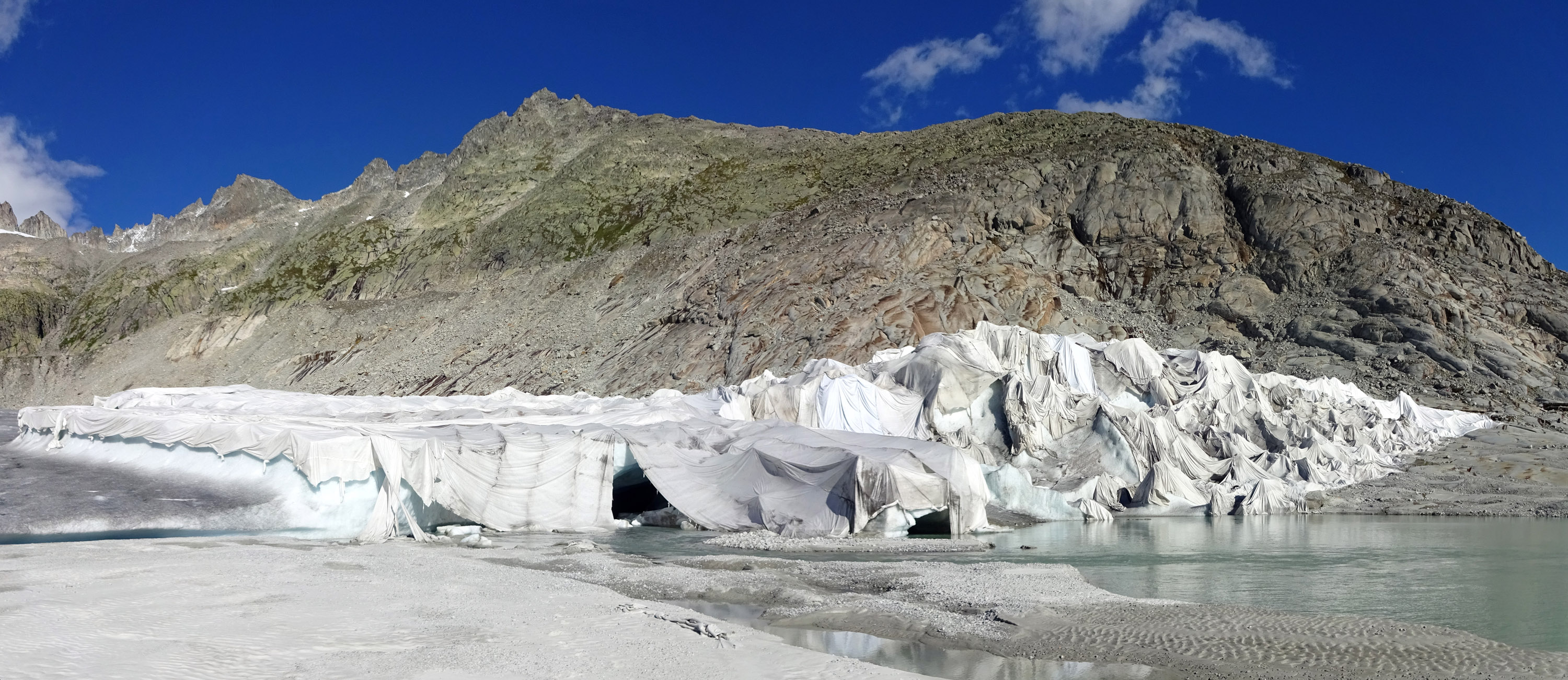 A glacier sits in front of a mountain side. The part of the glacier in the frame is covered by geotextile fabrics.