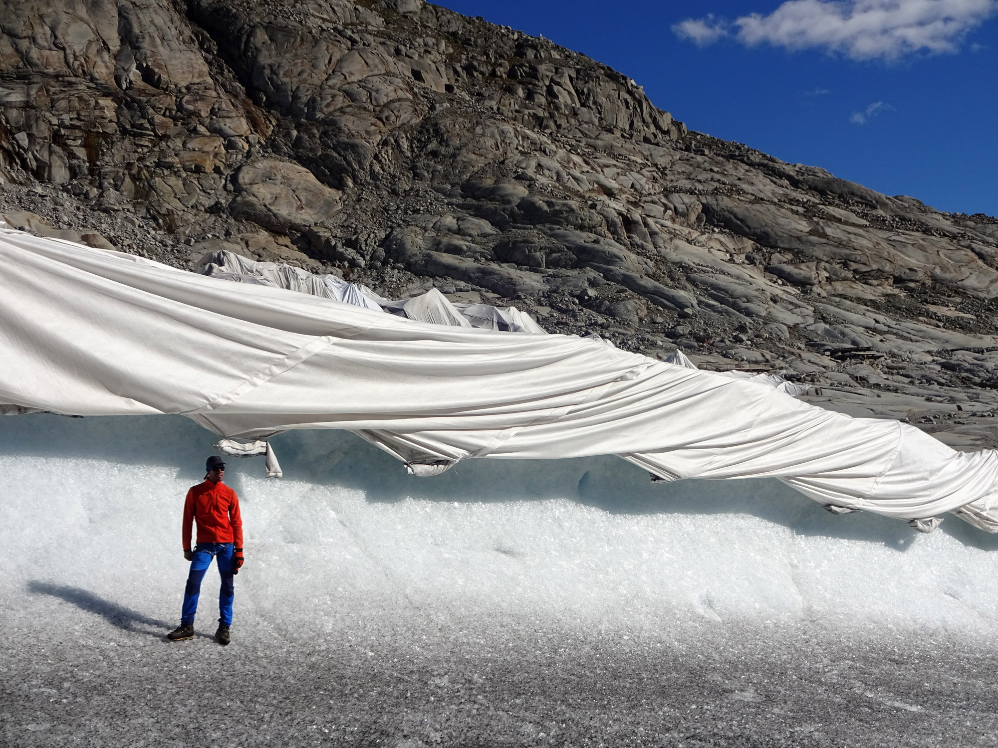 A person in a red coat stands in front of ice two times his height. The ice is covered with a white blanket.