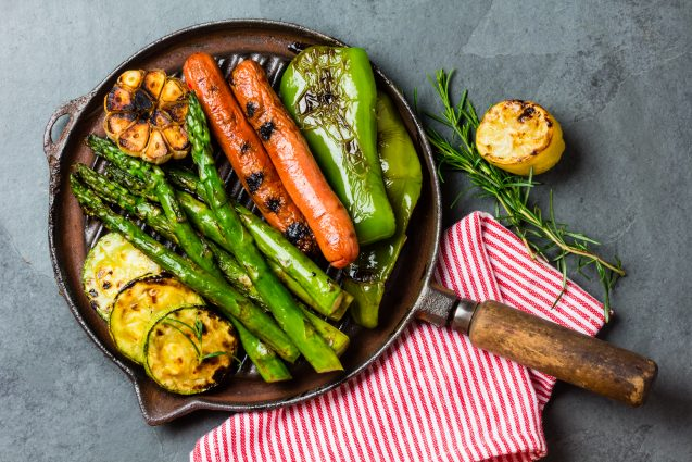 Grilled sausages and green vegetables - zucchini, asparagus, bell pepper, garlic, lemon and rosemary on cast iron grill pan