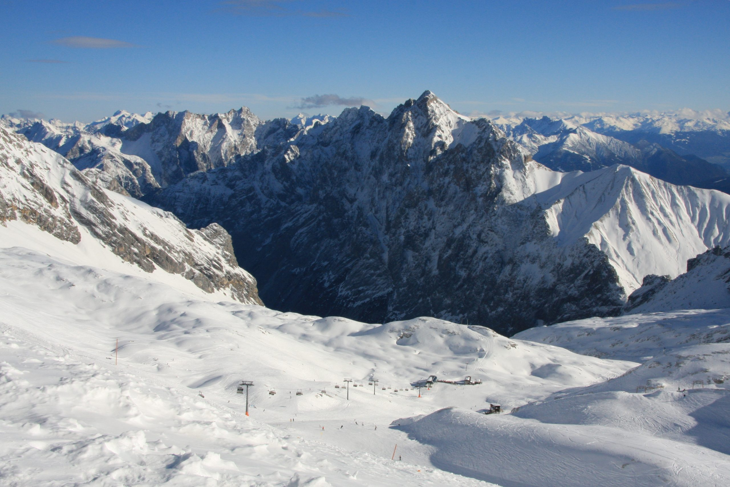 A snowy mountain range with ski lifts set against a blue sky.