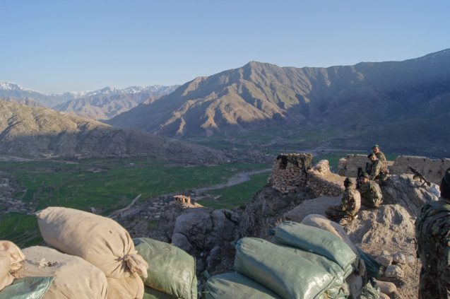 soldiers look out over mountainous terrain