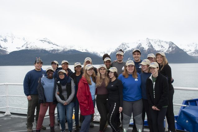 group photo aboard a ship with glaciers in the background