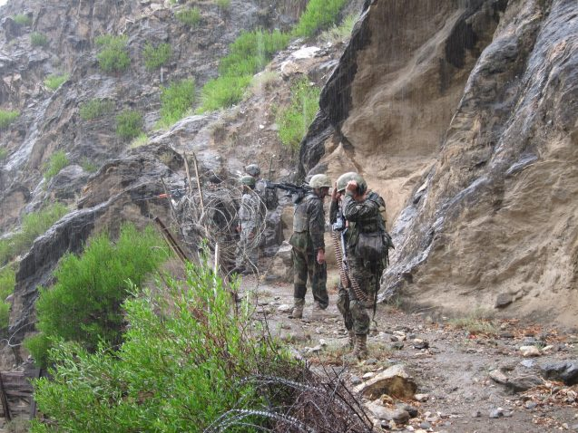 soldiers walking along narrow trail