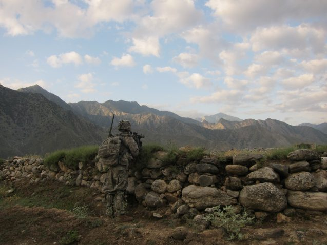 A soldier stands facing the valley and the mountains.