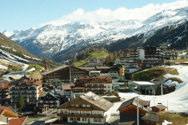 A city is situated in a snow-capped valley with snow-capped peaks behind it.