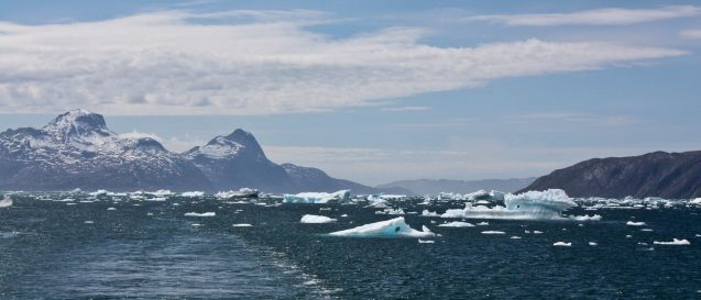 An expanse of deep blue water is dotted by light blue and white icebergs.
