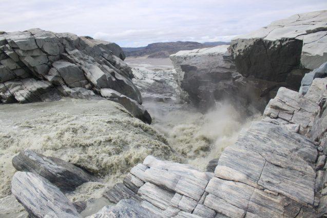 Grey water crashes through geometric pale grey rocks.