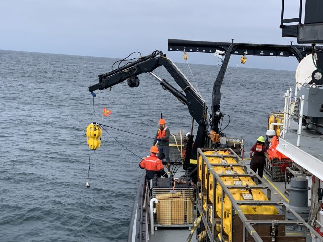 a crane lifts a yellow sensor out of the ocean
