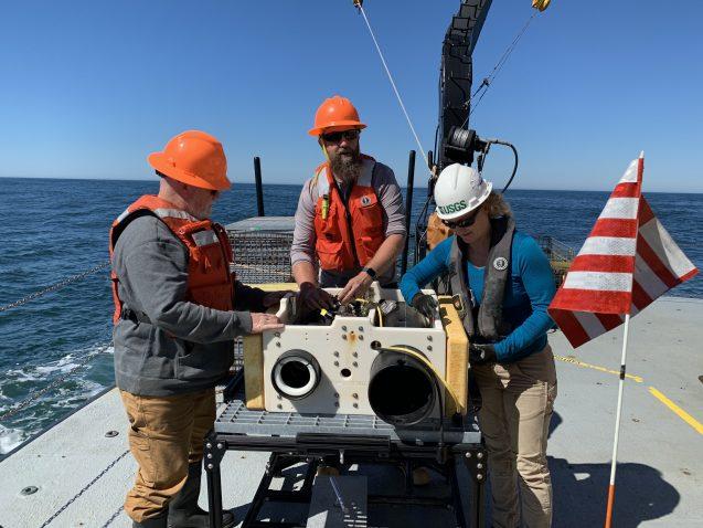 scientists in hardhats prepare large sensor